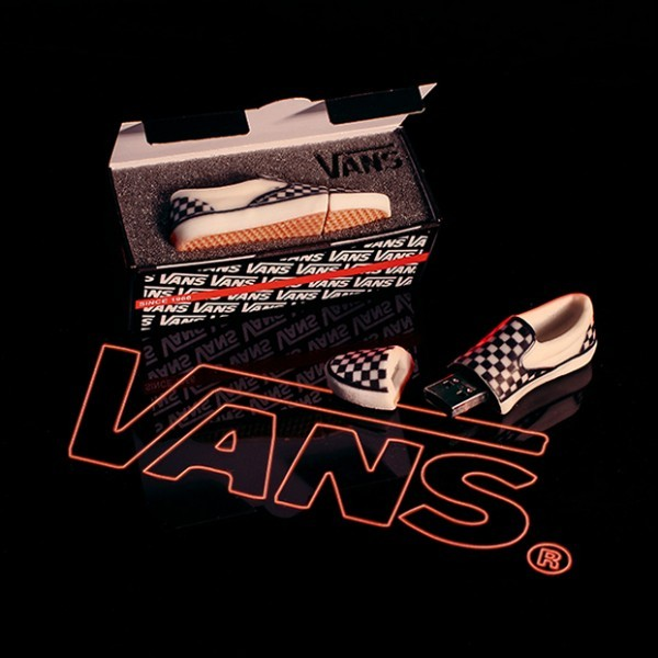 A product shot of custom miniature vans shoe USBs on a reflective black surface
